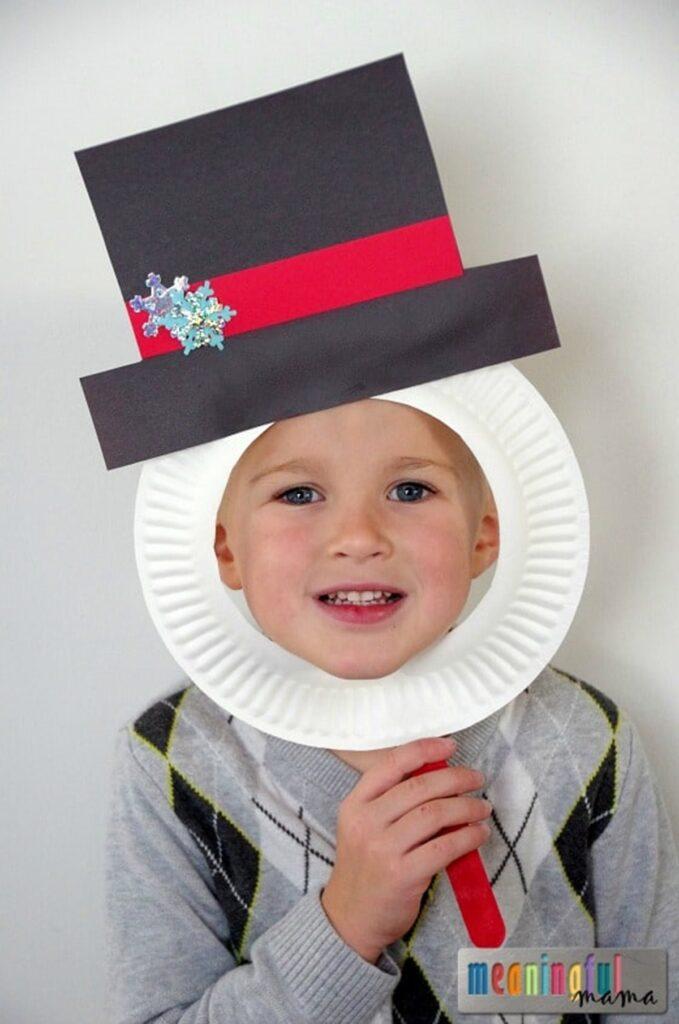 Kid behind paper plate snowman cutout
