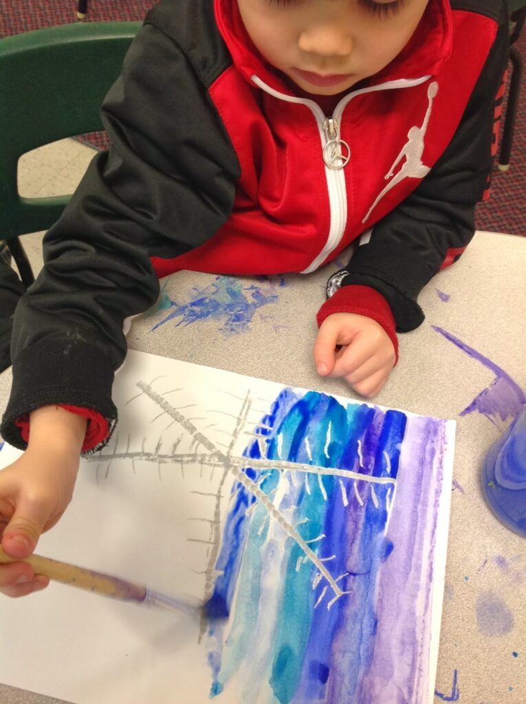Kindergartner painting with watercolors around a snowflake